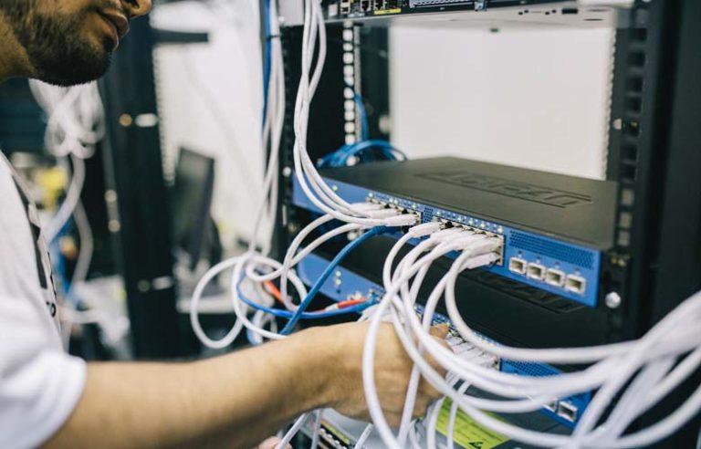 Tekniker skifter netkabel i rack